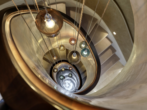 Encapsulating hanging lights with a bespoke curved stair